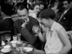 1920s B/W HA MS Man and woman talking and laughing at outdoor cafe with women in background / Paris, France