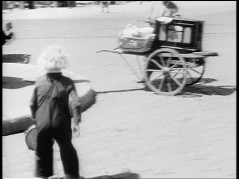 B/W 1920s child with tambourine spinning + dancing on cobblestone street / Paris / documentary