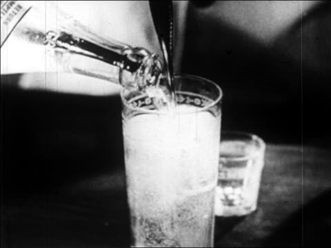 B/W 1920s close up glass filling up with liquor / newsreel