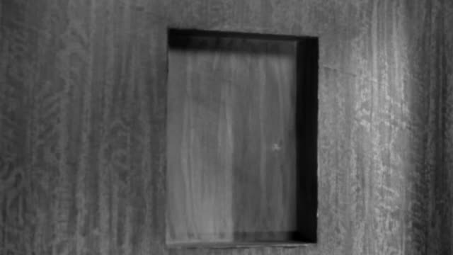 1920s close up small hatch window on door opening / man looking out