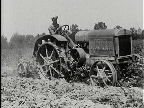 1920s MS PAN farmer driving old tractor and plowing crops