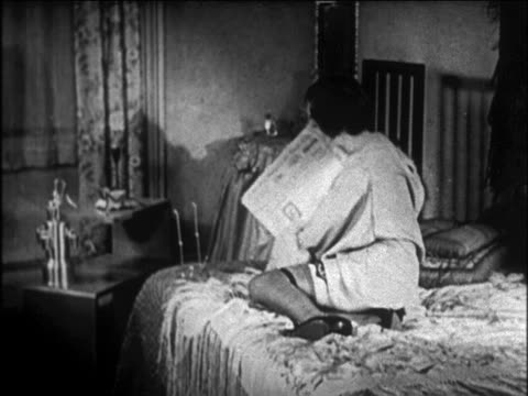 B/W 1920s flapper lying on bed reading newspaper with holding invention / newsreel
