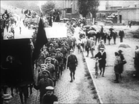 B/W 1920s high angle crowd carrying signs flags marching in street / Germany / documentary