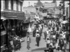 B/W 1920s high angle people walking by buildings at Coney Island / NYC / newsreel
