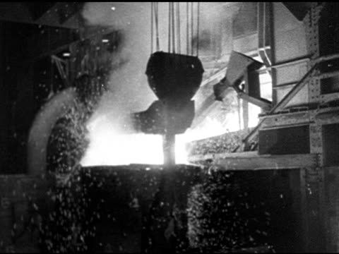 INDUSTRY WS Sparks flying from molten material in vat possibly steel mill MS Press slamming down on hot material lots of smoke light