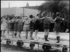 B/W 1920s line of women in swimsuits (1890s to 1920s) posing on platform over pool outdoors