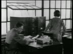 B/W 1920s man at desk tells woman to get file from cabinet / they discuss it then sit down / news.