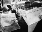 B/W 1920s man putting arms around 2 women on park bench as they read newspapers / newsreel