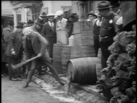 B/W 1920s man smashing wooden barrel as crowd looks on / Prohibition / feature film