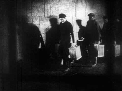 B/W 1920s men carrying boxes of bootleg liquor along wall / Prohibition / newsreel
