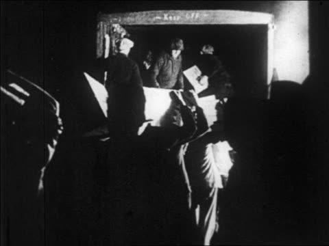 B/W 1920s men loading truck with boxes of bootleg liquor / Prohibition / newsreel