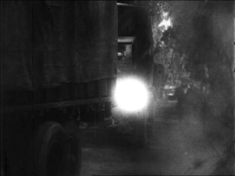 B/W 1920s men with guns hijacking row of trucks with bootleg liquor on rural road / Prohibition / news.