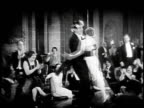 1920s MONTAGE Couple dancing at party, woman faints / United States