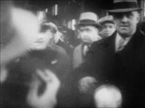 B/W 1920s police escorting gangster Legs Diamond thru crowd as photographers take photos / newsreel