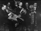 RADIO Unidentified male behind microphone then walking away band playing BG PAN Unidentified Jazz band playing music one male standing plucking...