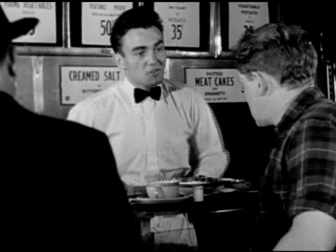 TIP FOR THE CUSTOMER DRAMATIZATION Young adult male working lunch counter waiter telling customer at counter to buy Tin saying he made fifty bucks on...