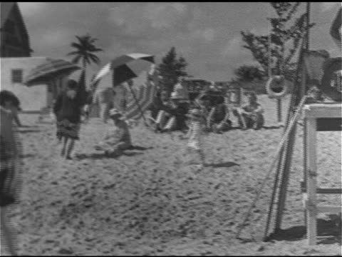VACATION WS Beach w/ people umbrellas MS Arthur Hammerstein throwing medicine ball on beach MS Agnes Mary Nolan sitting w/ unidentified woman...