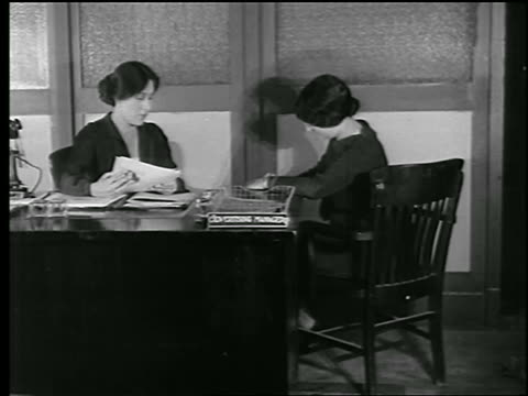 B/W 1920s woman at desk dictates to secretary who writes on pad of paper / woman answers telephone