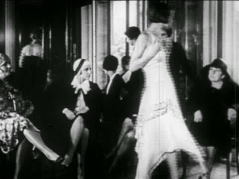 B/W 1920s woman modeling dress for seated women shopping / Guerlain, Paris / newsreel
