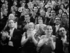 B/W 1920s/30s audience in formalwear clapping in theater