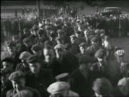 B/W 1920s/30s high angle male blue collar workers in caps walking towards camera to enter factory