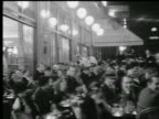 B/W 1920s/30s people at tables in crowded sidewalk cafe at night / Paris, France
