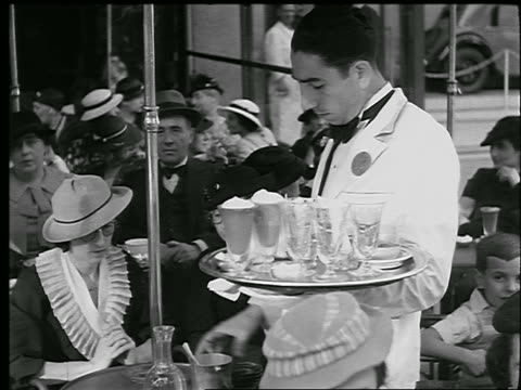 B/W 1920s/30s MS tilt down waiter with tray serving woman at table in crowded sidewalk cafe / Paris, France