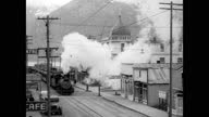 ALASKA RAILROAD Workers hammering on rail male driving spike to hold rail repairs 'Anchorage' sign on building HA WS Steam train pulling into town...