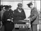B/W 1930s Amelia Earhart standing with policeman with fingerprinting equipment / newsreel