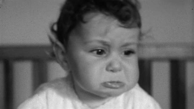 1930s black and white close up baby frowning and pouting