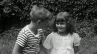 1930s black and white medium shot young boy kissing young girl / laughing