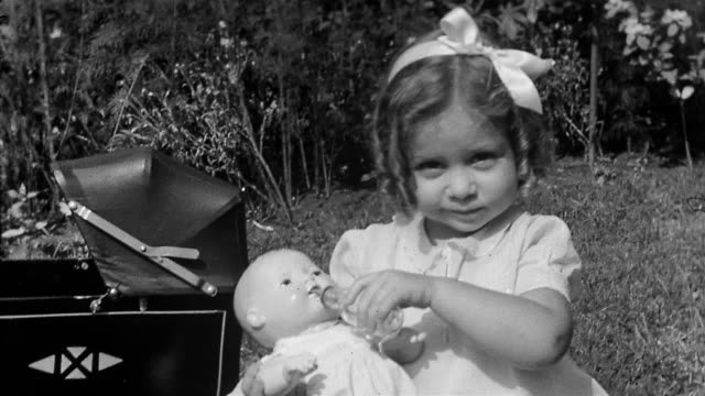 1930s black and white medium shot young girl with curls and bow in hair feeding + kissing baby doll / baby carriage in background