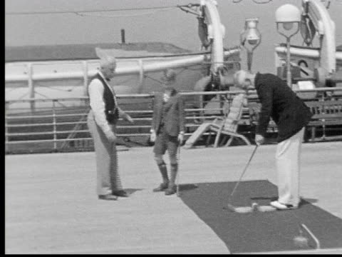 1930s B/W WS boy putting with two older men on deck of ship