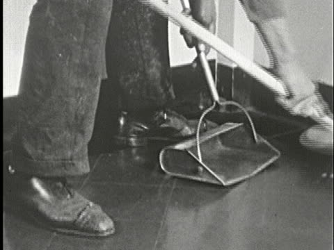 1930s B/W CU, Low section of man sweeping floor into dust pan