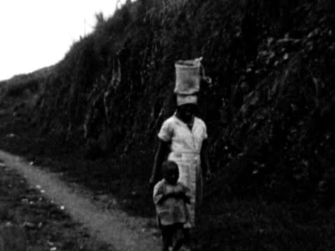 1930s B/W MONTAGE Woman with basket on head walking down path with young boy / Haiti
