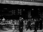 1930s B/W WS Pedestrians walking past patrons seated at the outdoor Florian cafe / Paris, France
