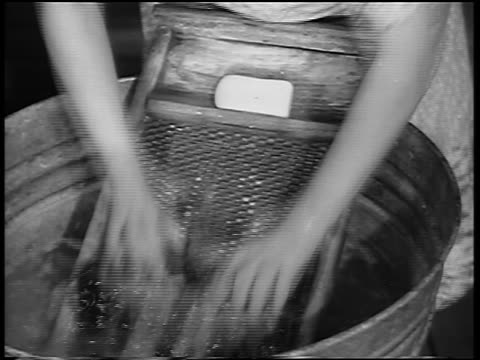 B/W 1930s close up woman's hands washing clothing on washboard in washtub