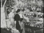 COMMONWEALTH of the PHILIPPINES ECONOMY People shopping in filled variety store w/ goods also hanging from ceiling child w/ adult male looking at...
