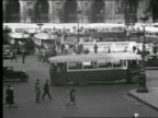 B/W 1930s high angle PAN bus in traffic through busy intersection / people walking on sidewalks / Paris