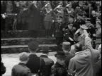 1930s TS Hitler walking down street saluting crowd and fellow officers / Germany