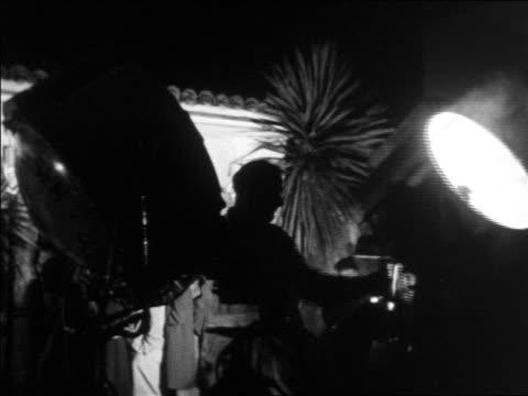 B/W 1930s man operating searchlight at Don Dickerman's Pirates Den nightclub / documentary
