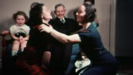 1930s medium shot 2 young women bobbing heads, hugging and making faces on floor / family in background