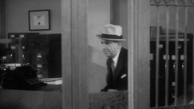 1930s medium shot tracking shot male bank robber holding up bank tellers, stuffing money into handbag and exiting
