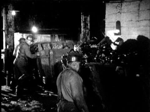B/W MONTAGE 1930s Miners underground loading mine cars of coal onto elevator, mine cart moving up elevator shaft, Maryland / USA