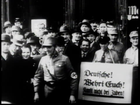 1930s MONTAGE AntiSemitic signs on buildings in Berlin including Brown Shirts chanting and holding Nazi flags / Germany