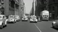 B/W 1930s REAR car point of view driving + parking on 5th Avenue with traffic + buildings / New York City