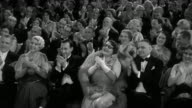 1930s wide shot elegantly dressed audience sitting in theater, smiling and clapping for performance