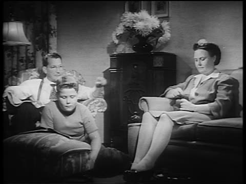 B/W 1930s/40s couple + boy sitting in living room listening to radio