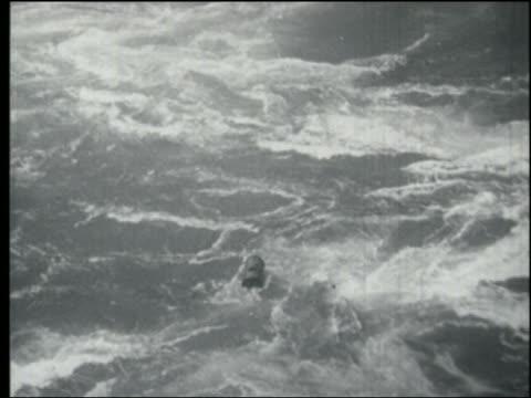 B/W 1930s/40s high angle tracking shot metal barrel floating in rapids / Niagara Falls