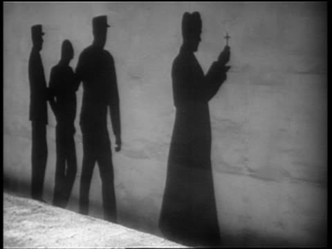 B/W 1930s/40s shadows of priest + death row inmate being led by prison guards / inmate stumbles